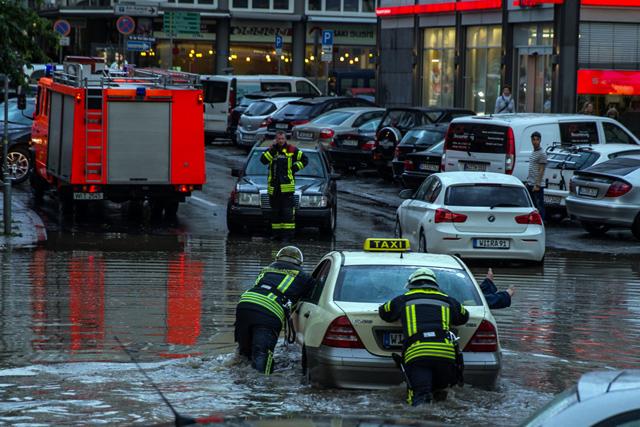 Feuerwehrleute schieben ein Auto von der überfluteten Straße