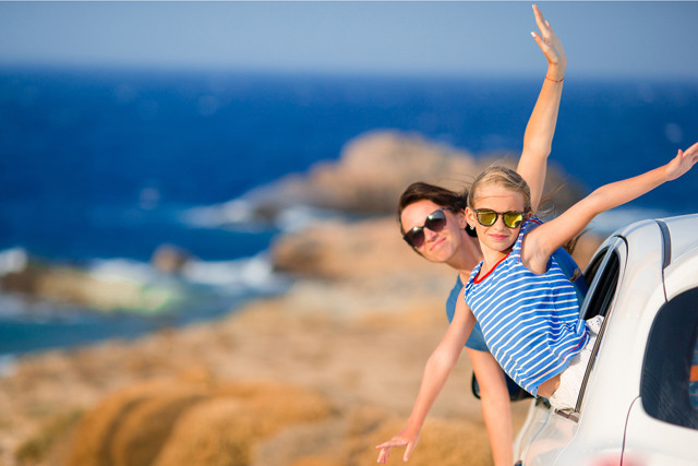 Mutter und Tochter mit Mietwagen im Urlaub