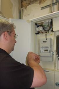 Letzte Handgriffe: Der Installateur verkabelt den neuen Stromzähler mit unserem Server.