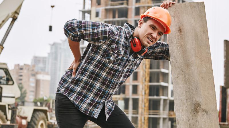Bauarbeiter mit Rückenschmerzen