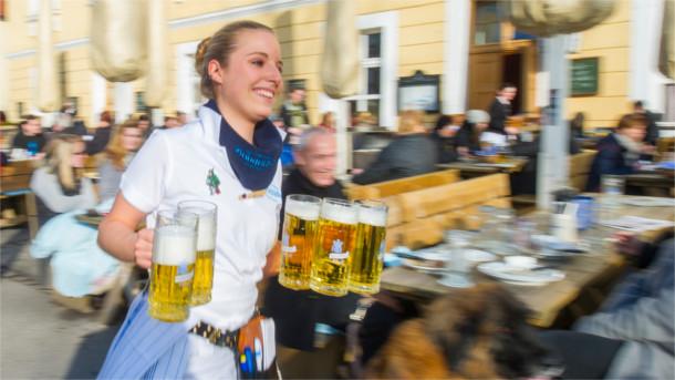 Frau kellnert im Biergarten