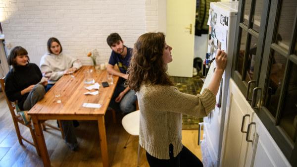 Die Studeninnen sitzen zusammen am Küchentisch. Sofie schreibt auf einem Zettel