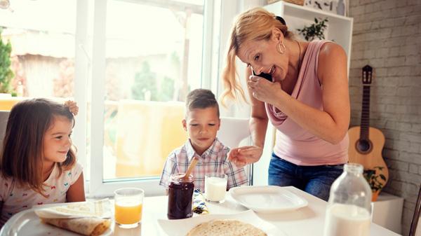 Mutter am Telefon während des Frühstücks