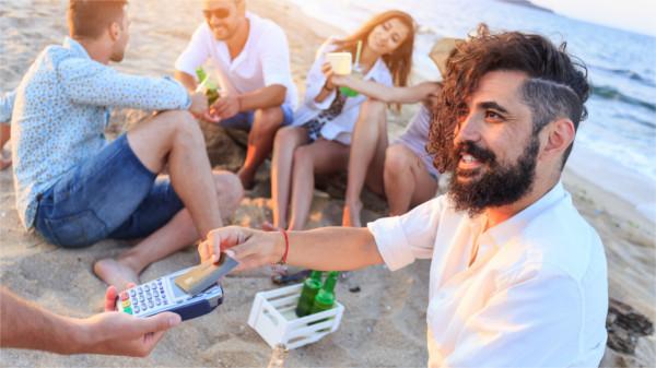 Mann zahlt am Strand