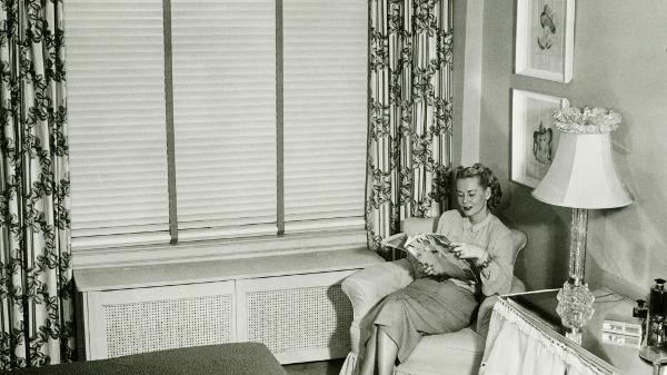 Frau liest in ihrer Wohnung eine Illustrierte