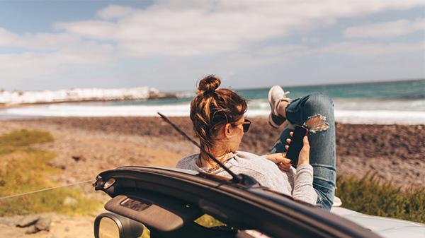 Junge Frau liegt auf der Haube ihres Autos und schaut auf ihr Handy