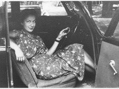 Eine Frau sitzt in einem Auto mit offener Tür und lächelt in die Kamera