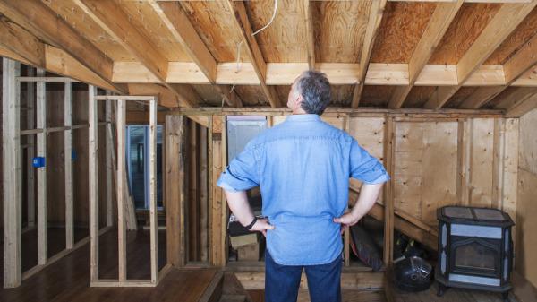Mann steht auf Dachboden und denkt über einen Ausbau nach