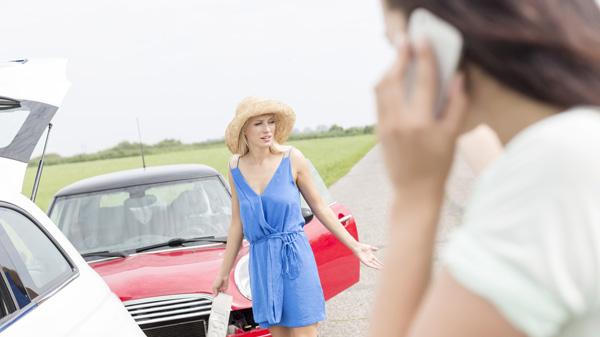 Eine junge Frau steht vor ihrem verunglückten Auto