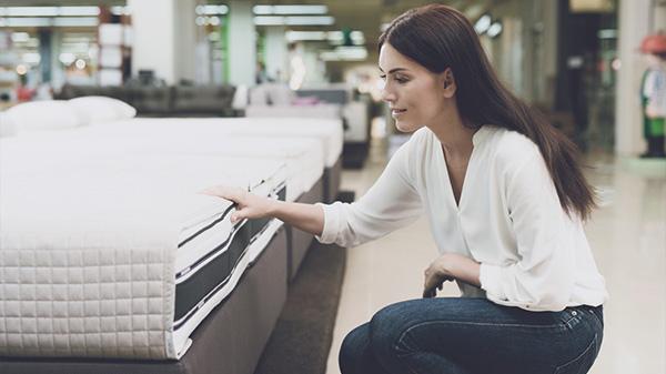 Eine Frau ist im Möbelhaus und will eine Matratze kaufen