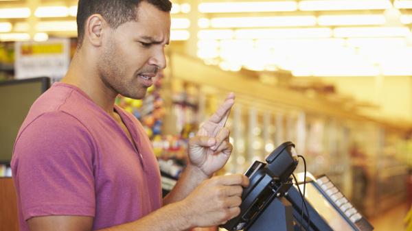 Mann steht im Supermarkt an der Kasse und hofft, dass seine EC-Karte funktioniert