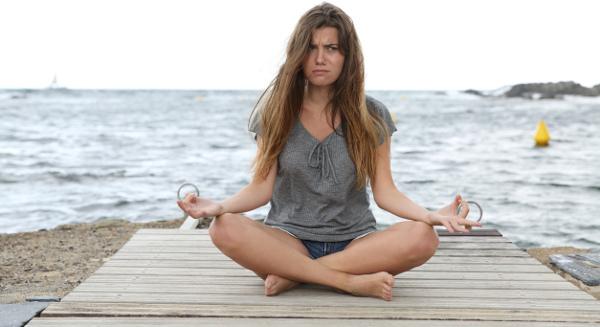 Frau sitzt am Strand und versucht zu meditieren, wird aber gestört