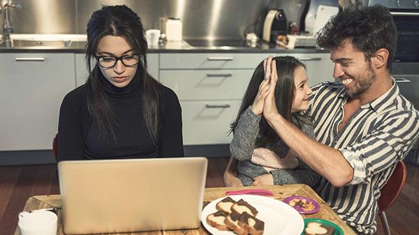 Mutter arbeitet mit Familie am Küchentisch