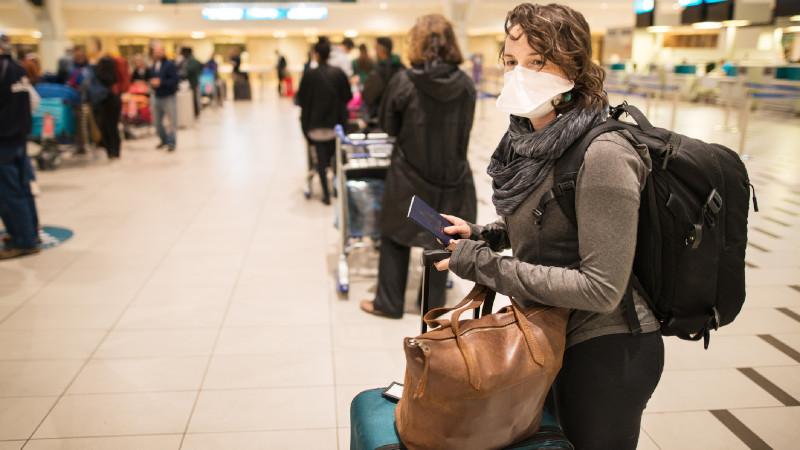 Frau am Flughafen mit Maske