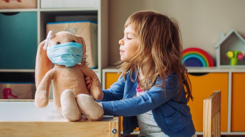 Mädchen spielt mit Stofftier mit Maske.