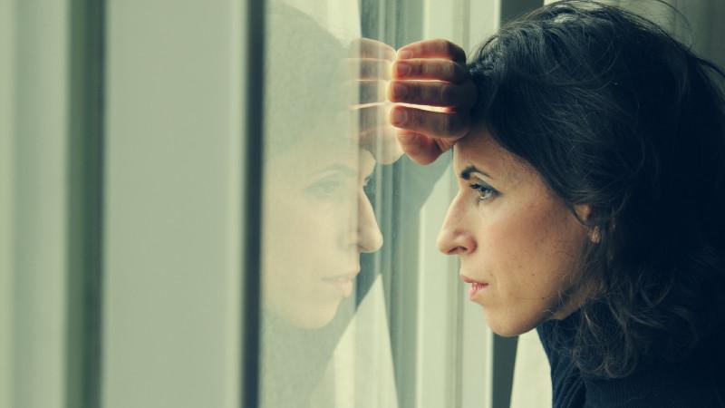 Frau blickt nachdenklich aus dem Fenster