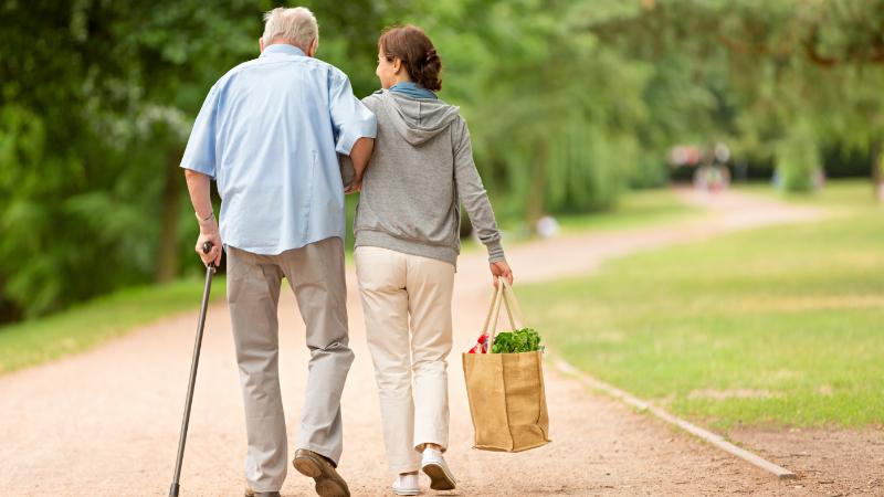 Älterer Herr und Pflegerin beim Spaziergang