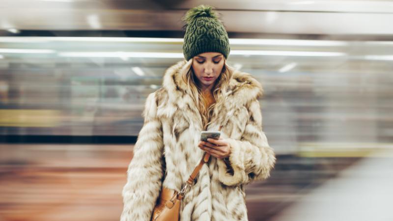 Frau benutzt Handy am U-Bahngleis