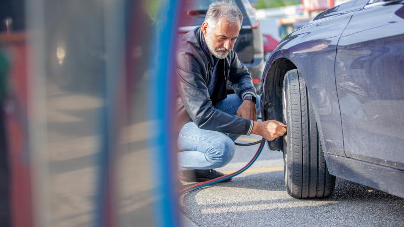 Mann beim Kontrollieren des Reifendrucks