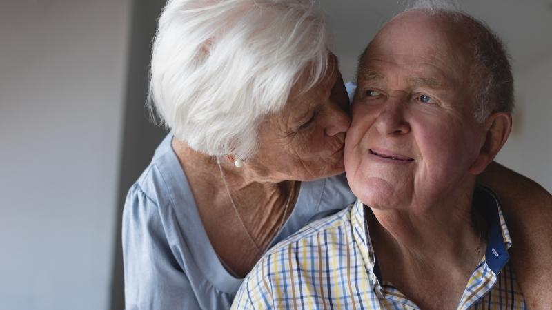 Pflegende Frau küsst Ehemann auf die Wange