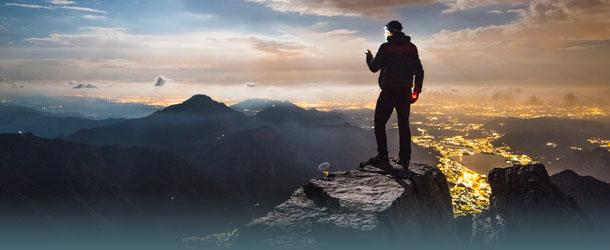 Mann auf einem Berg sucht Handyempfang