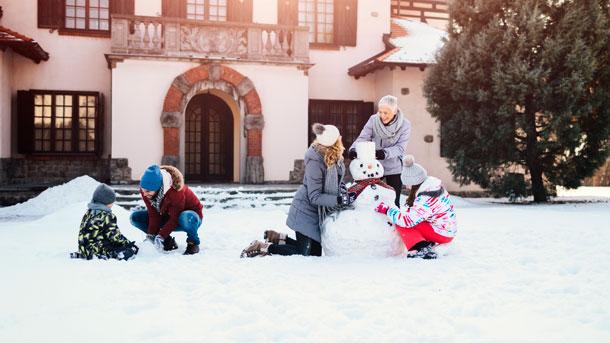 Familie beim Schneemann bauen