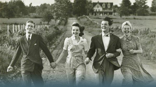 Zwei Paare laufen einen Landweg entlang